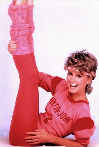 Olivia Newton John wearing leggings, leg warmers, T-shirt and headband.