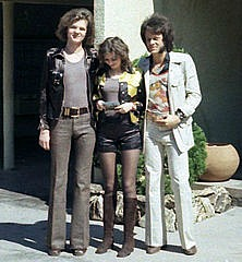 Two men wearing flares with a girl wearing hot pants