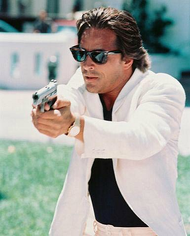 Don Johnson is his legendary white suit and ray ban sunglasses, pointing his gun at a villain