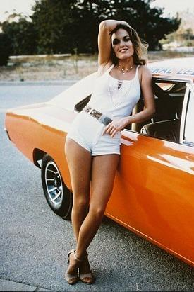 Catherine Bach (Daisy Duke) posing next to the General Lee from The Dukes Of Hazzard