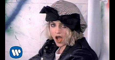 Madonna in the video for Borderline with striped hat and big black bow