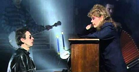 Shane MacGowan and Kirsty MacColl singing at the piano.
