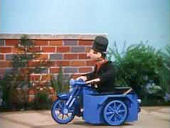 Roger Varley the chimney sweep riding his motorcycle with sidecar